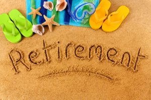 The word Retirement written on a sandy beach, with scuba mask, beach towel, starfish and flip flops (studio shot - warm color and directional light are intentional).